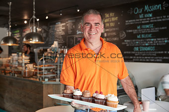 Portrait Of Male Owner With Tray Of Muffins In Coffee Shop