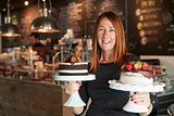Portrait Of Female Owner With Cakes On Stands In Coffee Shop