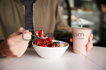 Close Up Of Man Eating Healthy Breakfast Of Granola In Cafe