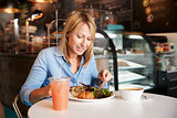 Woman In Coffee Shop Sitting At Table Eating Healthy Lunch