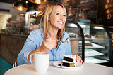 Woman In Coffee Shop Sitting At Table Eating Slice Of Cake