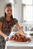 Girl puts challah bread on table for Shabbat meal, vertical