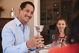 Jewish man holding kiddish cup blesses family at Shabbat