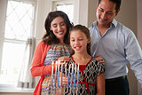 Parents watch daughter light candles on menorah for Shabbat