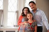 Jewish parents and daughter smiling, lit candles on menorah