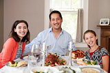 Jewish family at Shabbat dinner table smiling to camera
