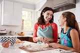 Jewish mother and daughter plaiting dough for challah bread