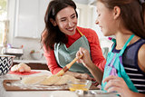 Girl brushing glaze on challah bread dough with her mum
