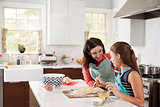 Jewish girl glazing plaited challah bread dough with her mum