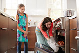 Mother taking bread out of the oven while daughter watches