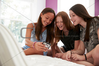 Three girlfriends on a bed using a smartphone, close up