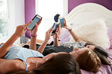 Three teenage girls lying on bed using smartphones, close up