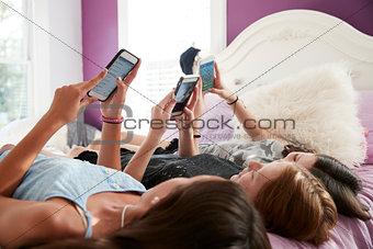 Three teenage girls lying on bed using smartphones, close up
