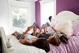 Three teenage girls lying on a bed using smartphones