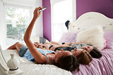 Teenage girl taking a selfie with two friends lying on a bed