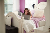 Teenage girl lying on her bed using a laptop computer