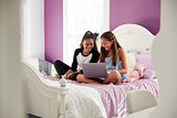 Two teen girls sitting on bed using laptop