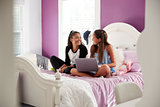 Two girls sitting on bed with laptop looking at each other