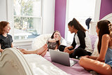 Four teen girls looking at phones and laptop in bedroom