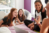 Four teen girls in bedroom looking at smartphone, close up