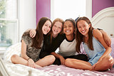 Four teen girls sitting on bed looking at camera, close up