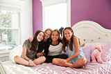 Four teen girls sitting on bed together looking at camera