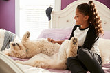 Young teen girl stroking pet dog on her bed