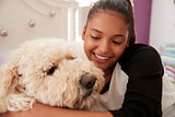 Young teen girl embracing pet dog on her bed, close up