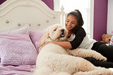 Young teen girl cuddling pet dog on her bed
