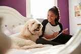 Young teen girl doing homework on her bed with pet dog