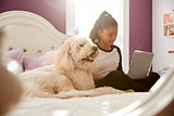 Young teen girl using laptop on her bed beside pet dog