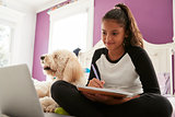 Young teen girl studying on her bed beside pet dog