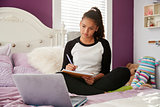 Teen girl sitting on bed watching computer and writing notes