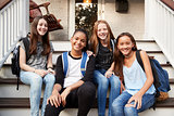 Young teen girls on front steps of house looking at camera
