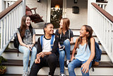 Young teen girls on front steps of house with school bags