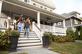 Four teen girlfriends walking down front steps of house