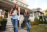 Young teen girlfriends leaving a house for school