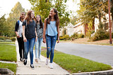 Four young teen girls walking to school together, front view