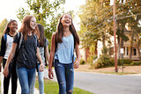 Four young teen girls walking to school, front view close up