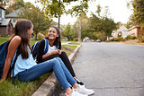 Two teen girlfriends sit talking at the roadside