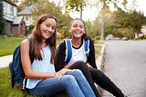 Two teen girlfriends sit at the roadside looking to camera
