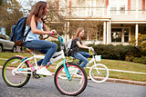 Two teen girls riding bikes in street, side view close up