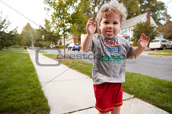 Toddler boy standing in the street making a face to camera