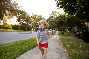 Toddler boy running in a quiet residential street