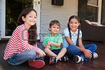 Portrait Of Children Sitting On Porch Of House Together