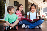 Group Of Children Sit On Porch Of House Reading Books Together