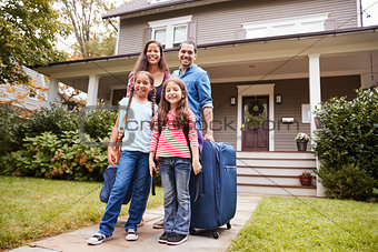 Portrait Of Family With Luggage Leaving House For Vacation