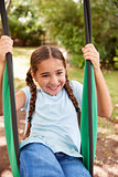 Girl Having Fun On Garden Swing At Home