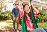 Father Pushing Daughter On Garden Swing At Home