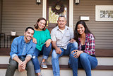 Parents With Adult Offspring Sitting On Steps in Front Of House